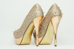 Gold high-heeled shoes. Stock Photos
