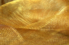 Gold Holiday Netting Fabric. Gold netting fabric used for holiday decor royalty free stock photography