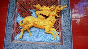Gold Holy Horse Bas-relief inside Pagoda in Vietnam. Closeup gold holy horse with dragon head bas-relief in pagoda against dark red background in traditional stock video