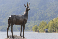 Gold Horned Chamois statue with Bohinj lake in background, Slovenia Stock Photos