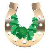 Gold horseshoe with clover Royalty Free Stock Images