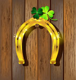 Gold horseshoe with Shamrock on wooden Royalty Free Stock Photo