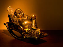 Gold Hotei seating in the rocking-chair. Hotei � chinese god of wealth, prosperity and happiness seating in the rocking-chair stock images