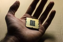 Gold i7 processor in hand. It`s a new Intel i7 processor with gold coating Stock Photo