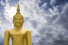 Gold image of Buddha with blue sky and cloud in background, light effect added ,thailand,filtered image,copy space. Gold image of Buddha with blue sky and cloud royalty free stock photos