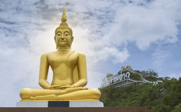 Gold image of Buddha with blue sky and cloud, mountain with temple on hilltop, light effect added in back of image of buddha Royalty Free Stock Images