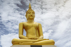 Gold image of Buddha with blue sky and cloud, mountain with temple on hilltop, light effect added in back of image of buddha Stock Photography