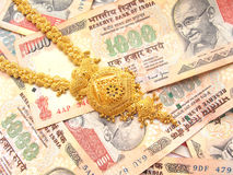 Gold And Indian Currency. Close up gold necklace on indian thousand rupees notes Stock Photography