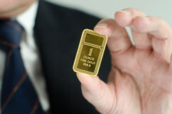 Gold Ingot. Gold bar held by a business man Royalty Free Stock Photos
