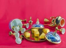 Gold ingot Gold jug Tea glass benjarong  on background. Royalty Free Stock Images