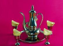Gold ingot Gold jug Tea glass golden plates red background. Gold ingot Gold jug Tea glass golden plates on red background stock photo