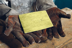 Gold ingot in hands Stock Photography