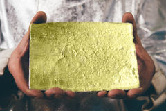 Gold ingot in hands Royalty Free Stock Photos