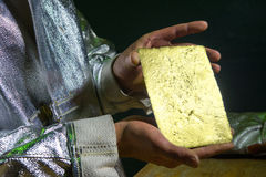 Gold ingot in hands Royalty Free Stock Photography