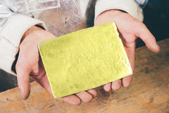 Gold ingot in hands Stock Image