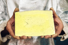 Gold ingot in hands Stock Images