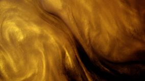 Golden ink or dust creating abstract cloud formations. Art backgrounds.