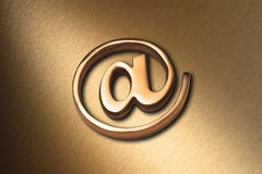 Gold @ Internet Email Background. A gold @ email alias symbol or at sign on a brushed bronze background Royalty Free Stock Image