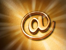 Gold At Internet Web Background. A gold email alias symbol or at sign on a brushed bronze background with rays of light coming out Royalty Free Stock Photos