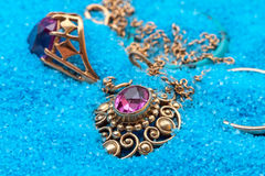 Gold Jewellery in blue sand Royalty Free Stock Photography