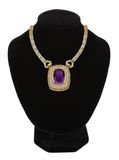 Gold jewellery necklace with violet stone Royalty Free Stock Photo