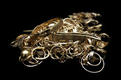 Gold jewelry. Pile of gold jewelry on black Royalty Free Stock Photos