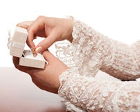 Gold jewelry. A white box with a gold jewelry in women's hands stock image