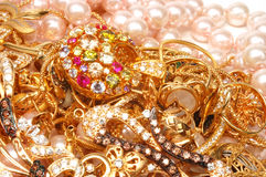 Gold jewelry. Yellow gold jewelry with stones  and pearls closeup Stock Images