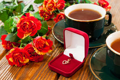 Gold jewelry, cups of tea and roses bouquet Royalty Free Stock Photos