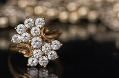 Gold jewelry with diamonds on black mirror surface. Royalty Free Stock Image