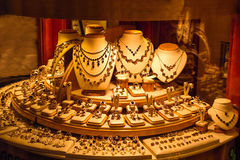 Gold jewelry display in store window. Brightly lit round store display of gold jewelry with window reflections royalty free stock images