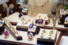 Gold jewelry with gems at showcase. Of jewelry shop Royalty Free Stock Photography