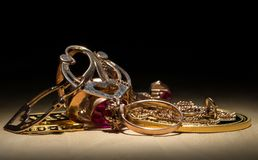 Gold jewelry, gold bars and coins are lit by a bright light against a dark background.  Stock Images
