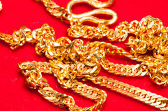 Gold jewelry. Necklace on red background royalty free stock images