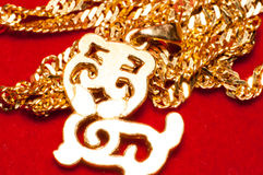 Gold jewelry. Necklace and a  tiger shaped Pendant on red background Royalty Free Stock Photography