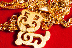 Gold jewelry. Necklace and a  tiger switch Pendant on red background Royalty Free Stock Image