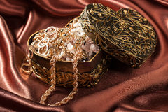 Gold jewelry and other decorations in decorative box heart shape Royalty Free Stock Photo