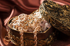 Gold jewelry and other decorations in decorative box heart shape Royalty Free Stock Photography
