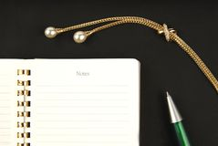 Gold jewelry, pen and notebook Royalty Free Stock Photography