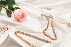 Gold jewelry, pink rose, wine glass stock images