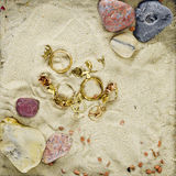 Gold jewelry in a scenery with sand Royalty Free Stock Photography