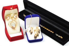 Gold jewelry sets. Inside a boxes, on white background Stock Photo