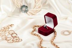 Gold jewelry on silk fabric Stock Photos