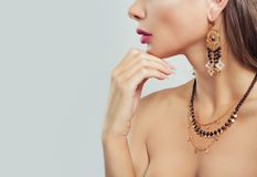 Gold jewelry on woman neck closeup. Necklace and Earrings. On female body on background with copy space royalty free stock image