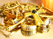 Gold jewels. Gold rings and necklaces over mirror surface Stock Images