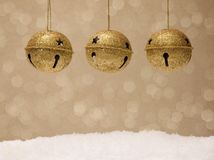 Gold Jingle Bells on a Golden Background. With light sand snow Stock Photography
