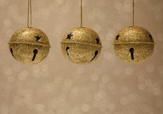 Gold Jingle bells on a Golden Background. With lights in the background Royalty Free Stock Photos