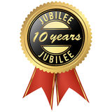 Gold jubilee seal. Seal colored black and gold with red ribbons for ten years jubilee Stock Photos
