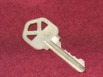 Gold key. Close up of a gold key on red Royalty Free Stock Photography