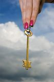 Gold key. In a hand against the cloudy sky Stock Photos